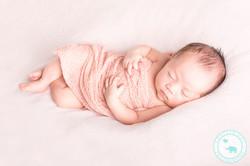 Newborn girl asleep on pink blanket