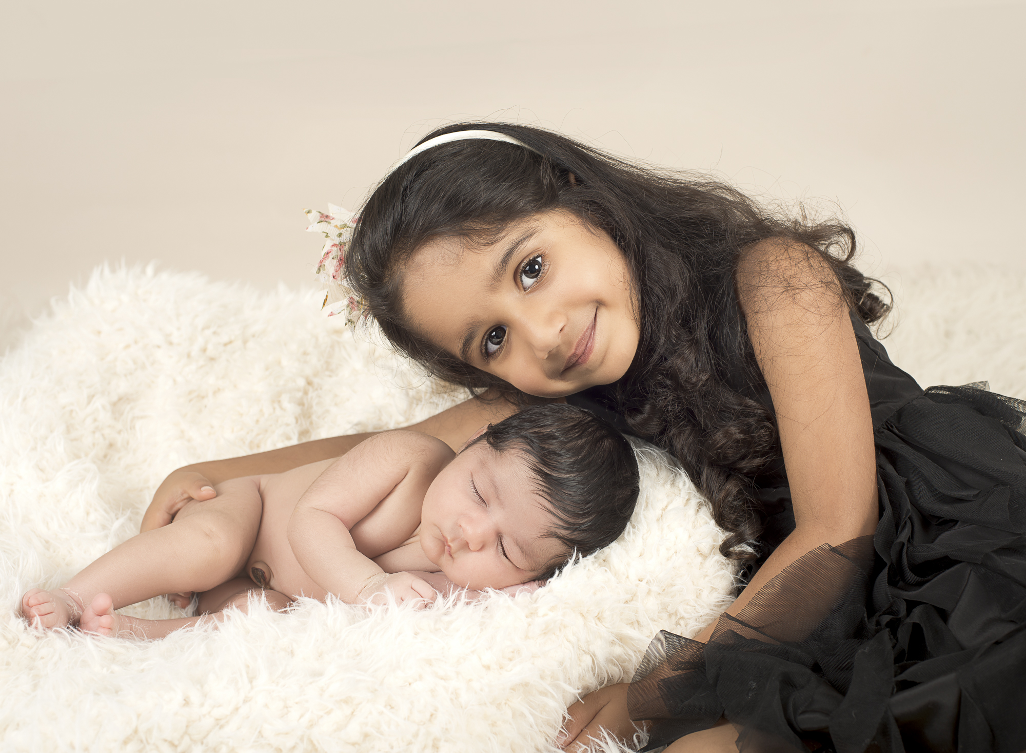 Newborn girl and sister in studio