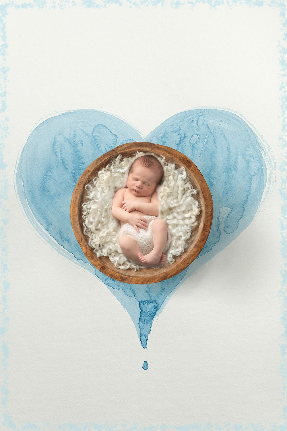 newborn boy in a heart nest blue
