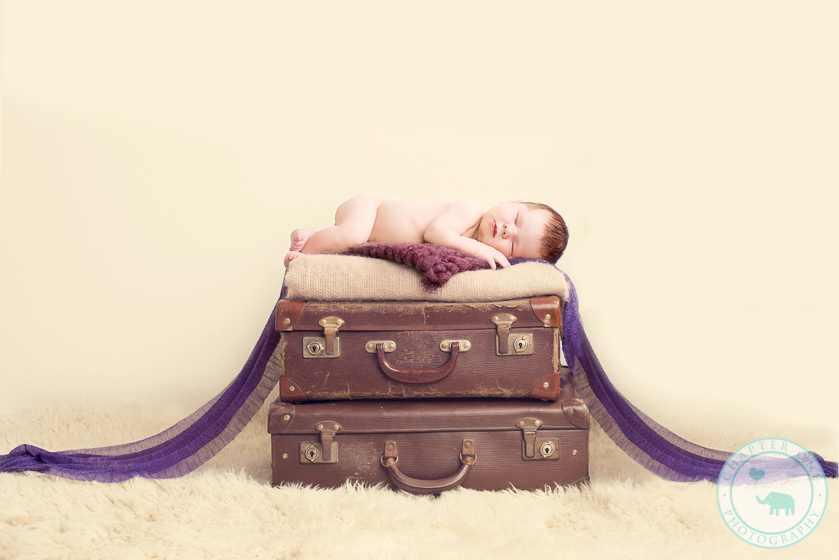 Newborn girl on suitcases