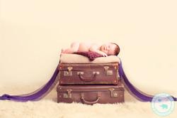 Newborn girl on suitcases