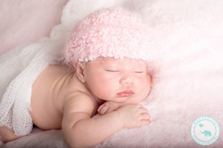 Newborn girl in pink beanie