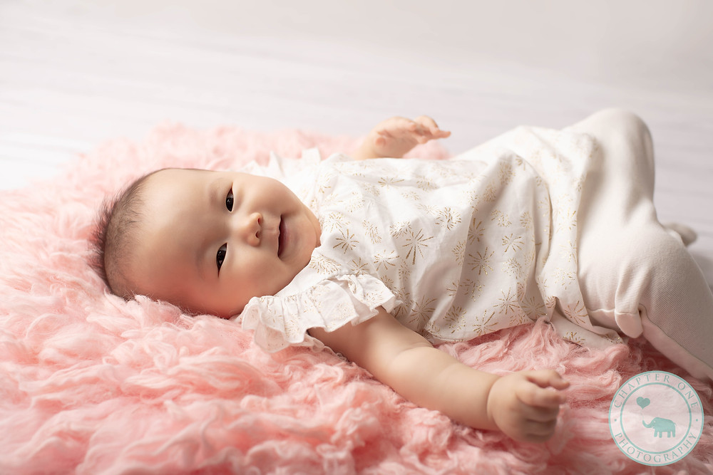 6 month baby girl on pink rug