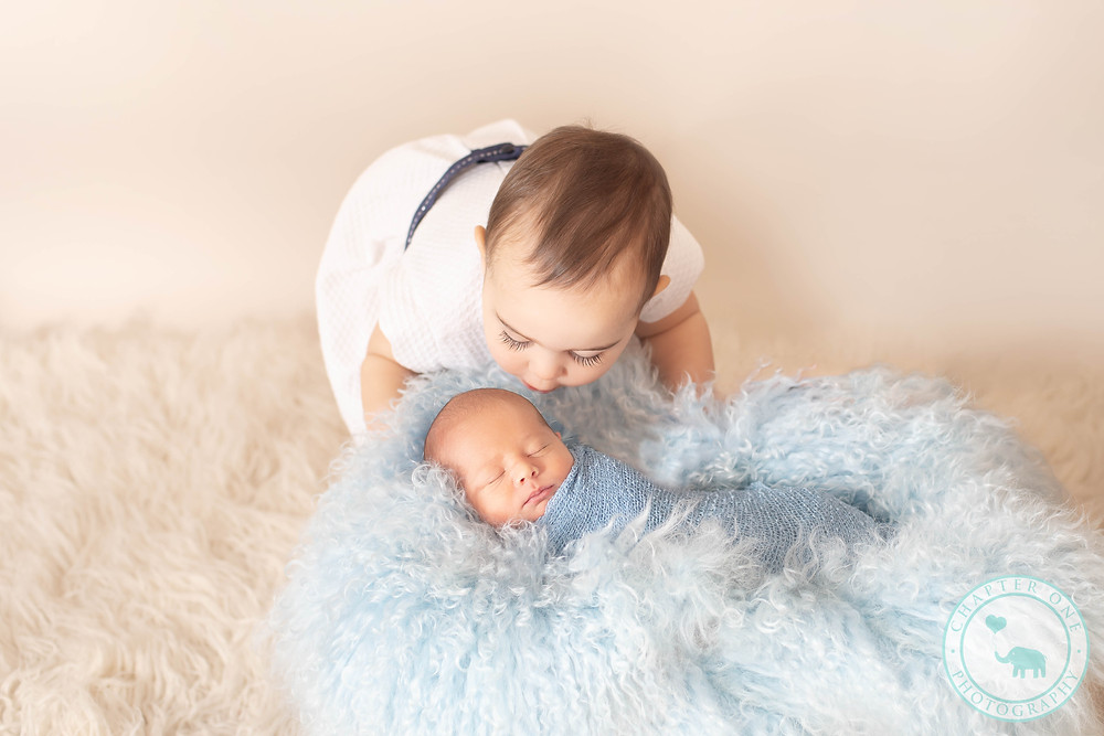 Newborn boy in blue fluff with big sister