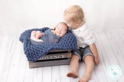 newborn boy and brother in studio