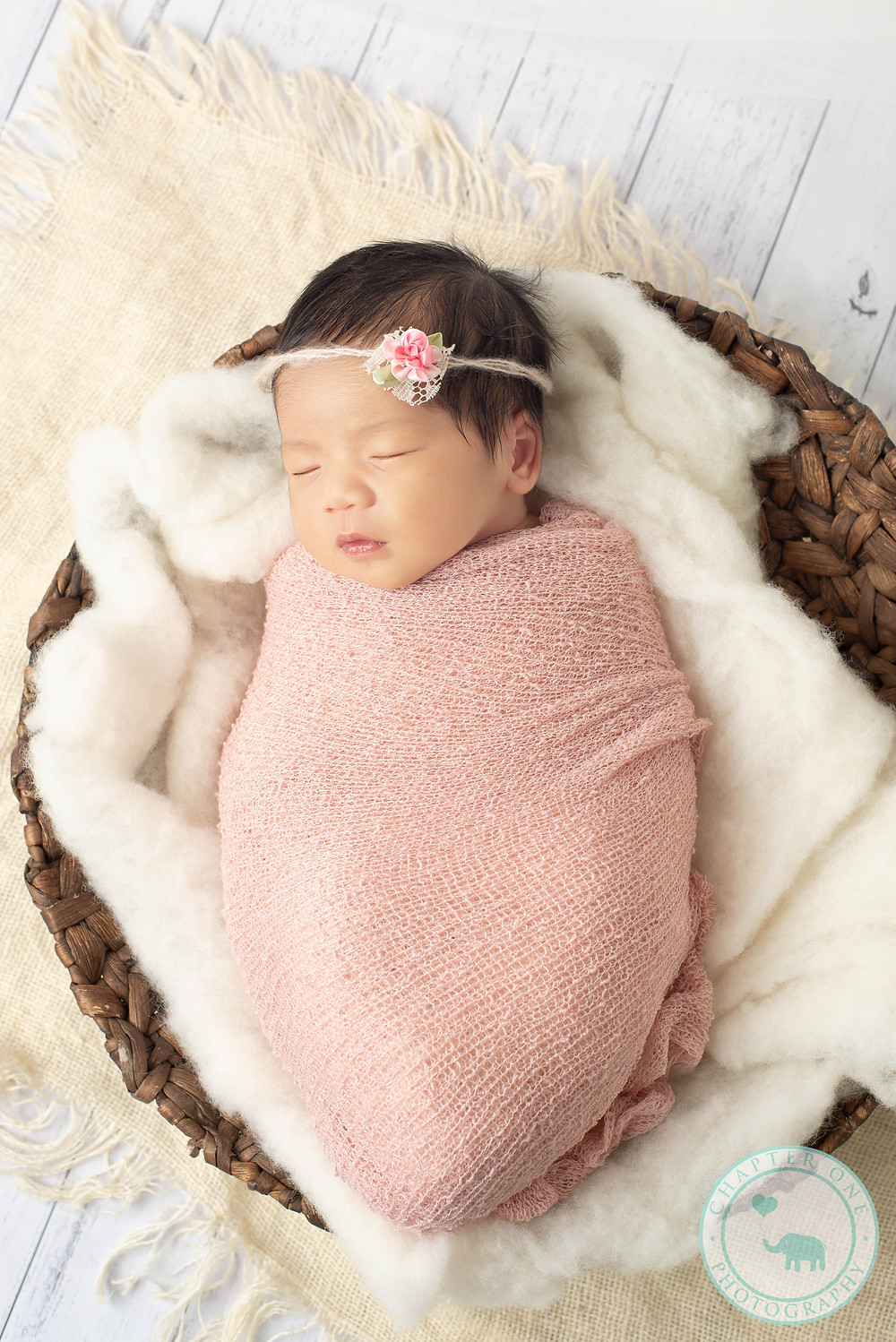 Sleeping newborn girl in basket with pink headband