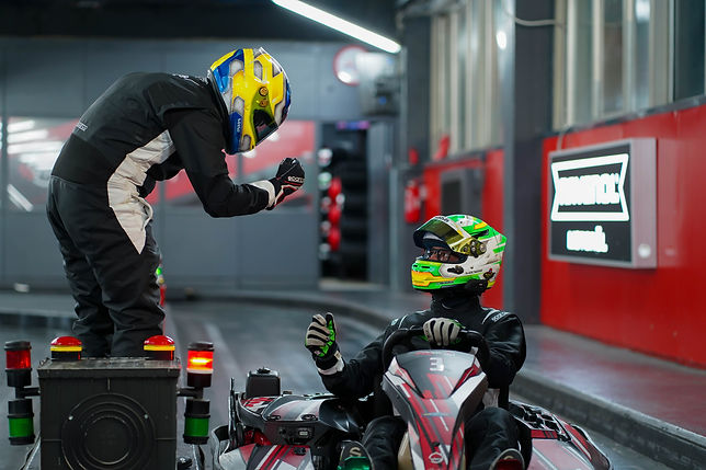 Compagni di squadra che effettuano un cambio pilota durante una corsa in kart Endurance Time VKI