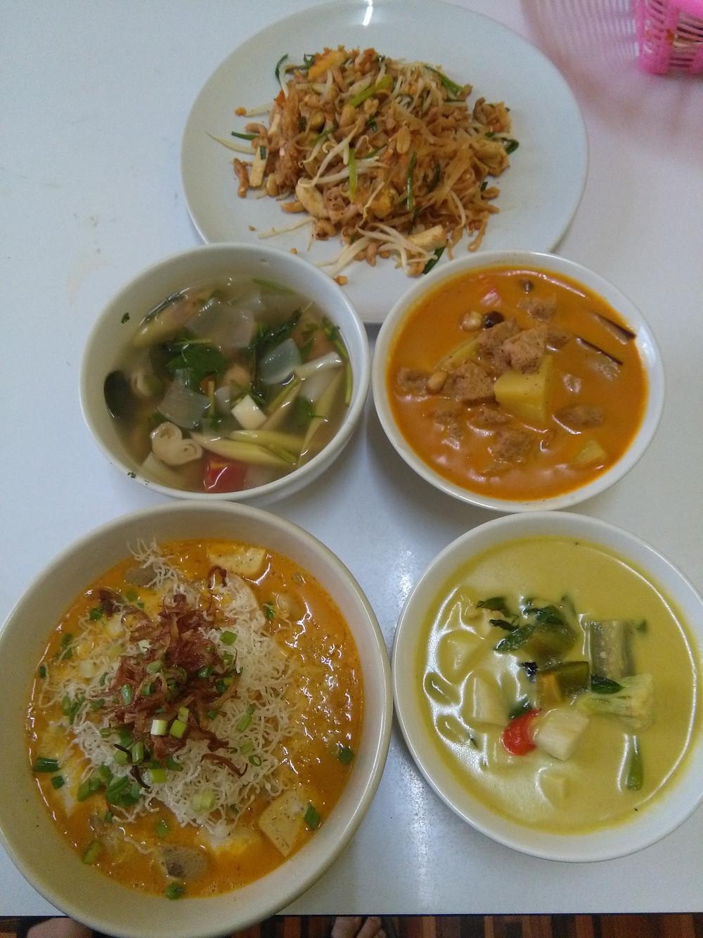 En haut: pad thai, au centre à gauche: soupe Tom Yum, au centre à droite: massaman curry, en bas à gauche: kao soy, en bas à droite: curry vert (tous véganes)