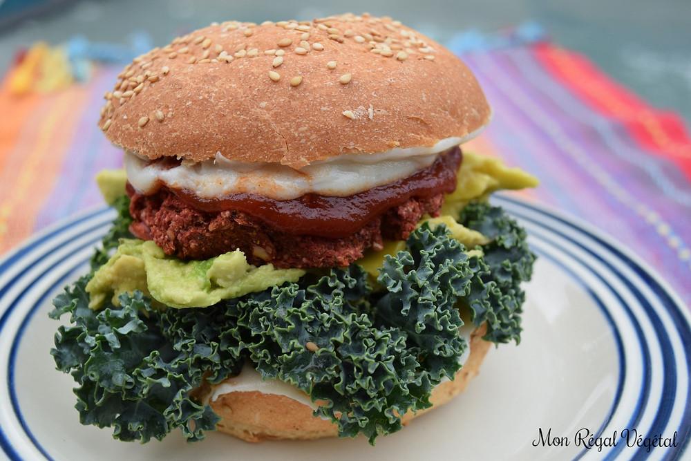 Mon burger servi dans un pain biologique au kamut et sésame (Inewa) avec du ketchup bio, de la végénaise, de l'avocat, du fromage végétal Daiya et du bon kale frisé