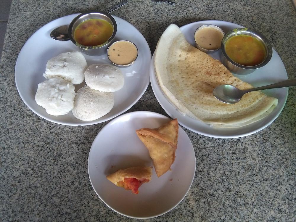 En haut à gauche: idlis (pains de riz fermentés) et leurs sauces, à droite: dosa (crêpe de farine) et sa sauce, en bas: samosas aux légumes et patates