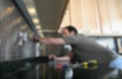 Tile installer grouting back splash in kitchen area.