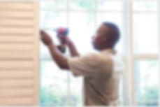 Handyman with a screw gun fixing a window