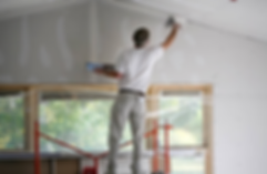 Man spackling ceiling corners while standing on platform.