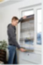Handyman installing window blinds