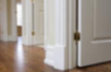 white base molding, brown hardwood floors, hallway area