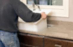 Handyman installing sink into counter top