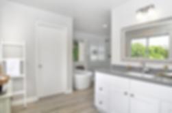 Updated bathroom. Gray counter tops, white door, soaking tub, wood tile floor