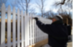 Outdoor painter painting a white picket fenence in the cold