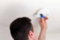 Man installing a battery into a smoke detector