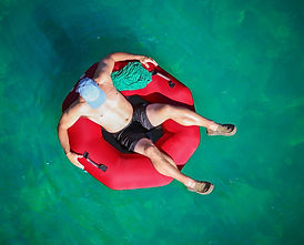 a man floating down a river in a blow up