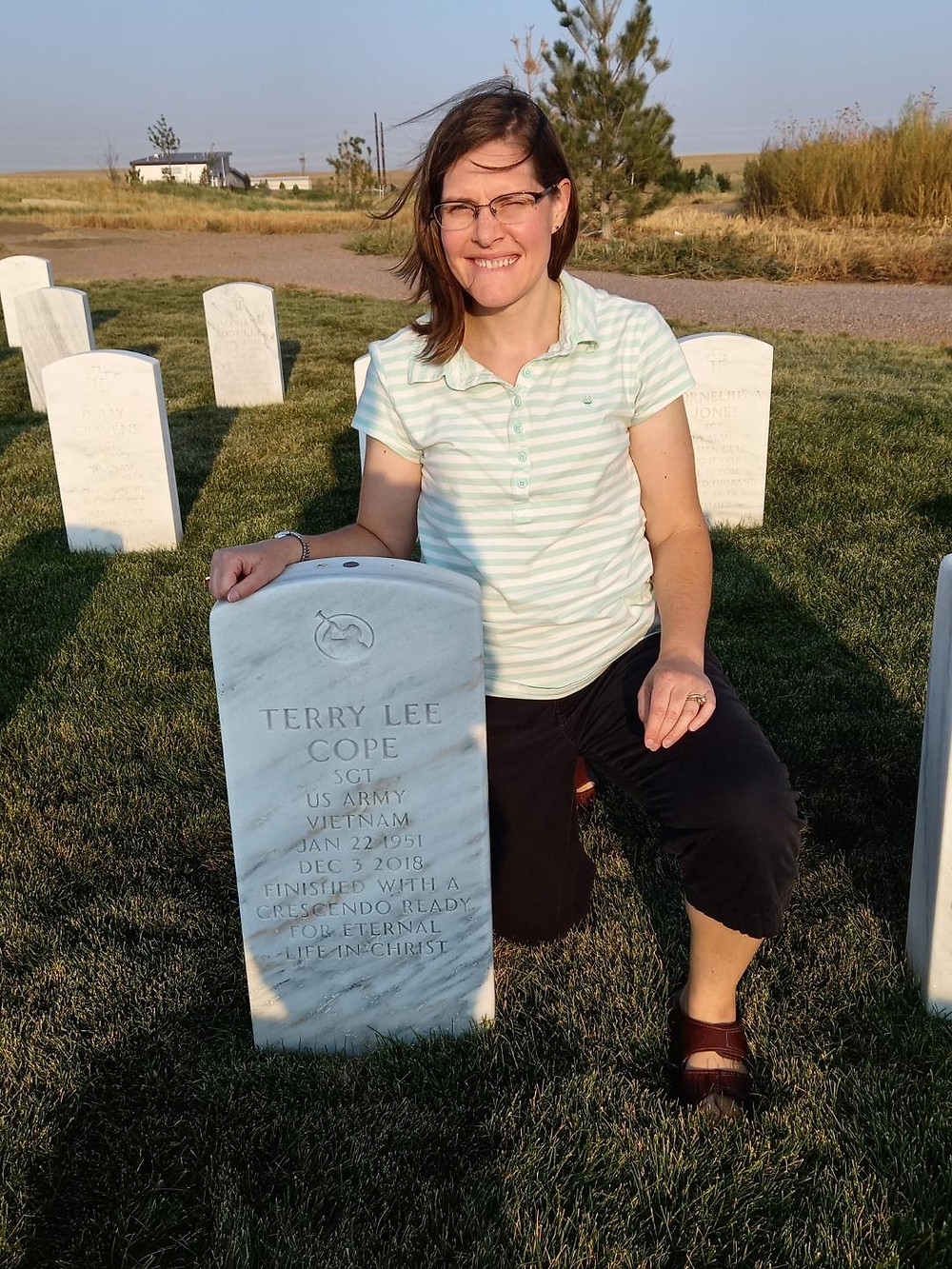 A woman kneels at a headstone in a graveyard.