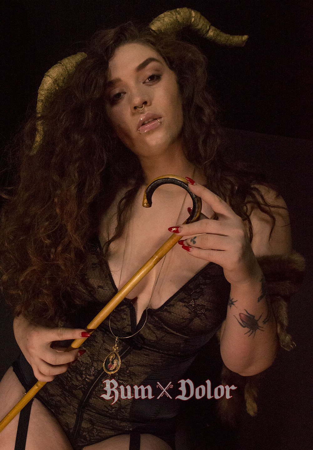 tattood redhead with curly hair holding a crop in lingerie