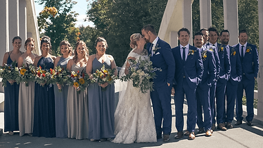 Bride and groom pose with bridesmaids an