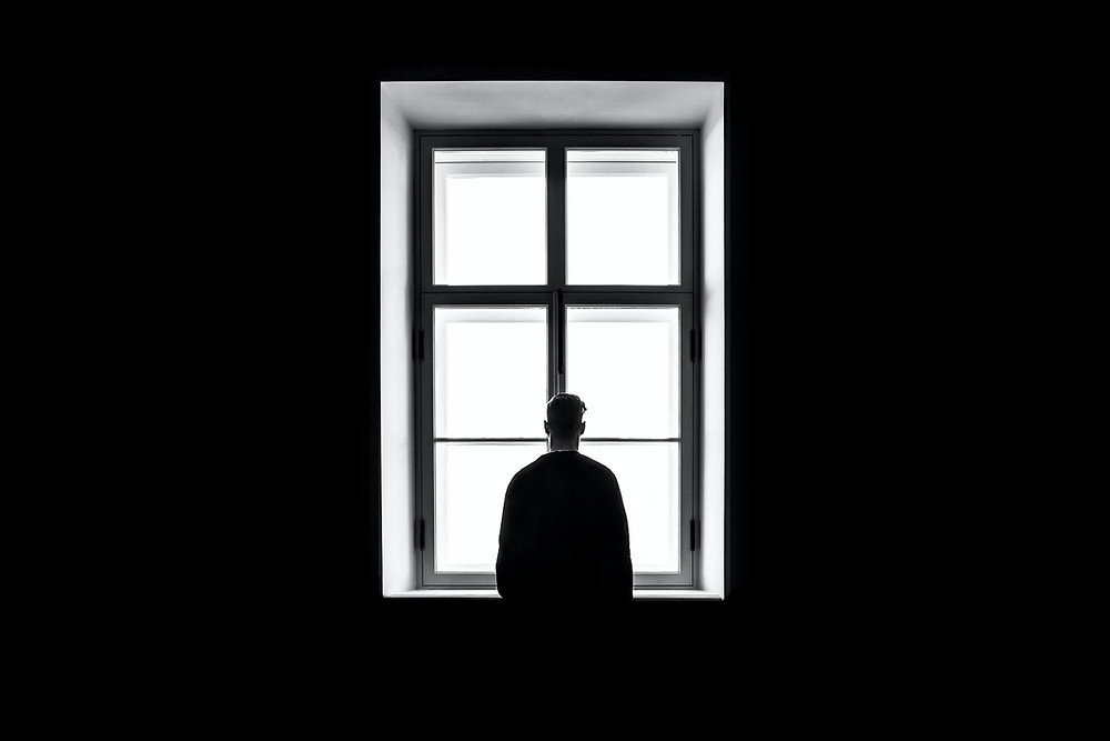 Gray, black, and white image showing person standing by themselves with their back turned to camera. They are looking outside of a window with light coming through.