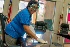 Desert Arc employee cleaning desk