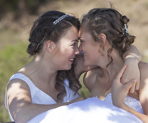 two brides smile and embrace in nature s