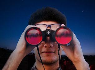 A person watches through binoculars.jpg