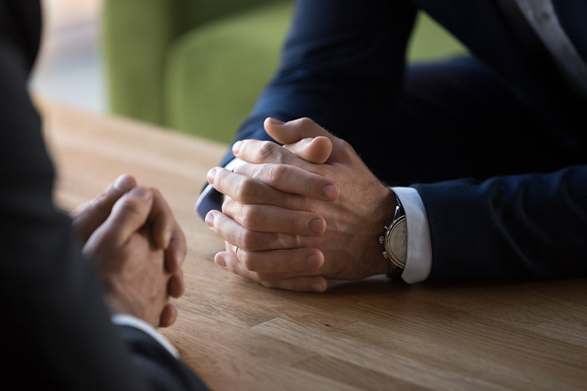 Clasped male hands of two businessmen ne