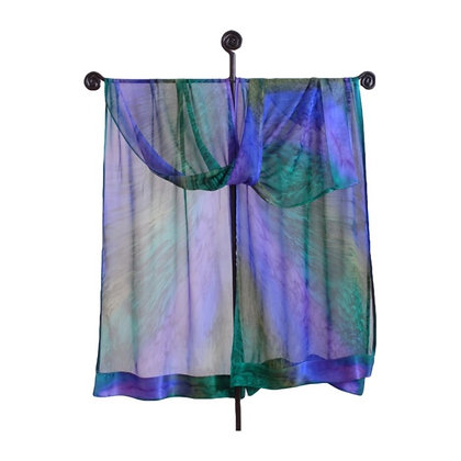 A beautiful sheer emerald green, turquoise blue and purple hand painted silk ruana hanging on a silver display rack