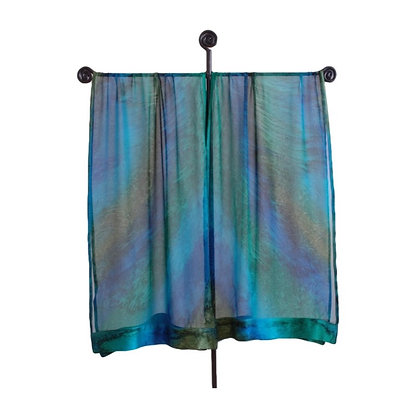 hand painted silk Ruana in an ombré of rich hues of turquoise mossy green and azure ocean blue on a tall silver display