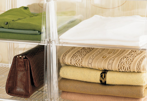 Sweaters folded neatly on shelves.png