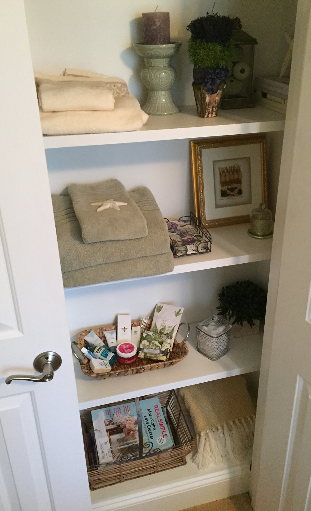 Closet shelves with towels, magazines and toiletries