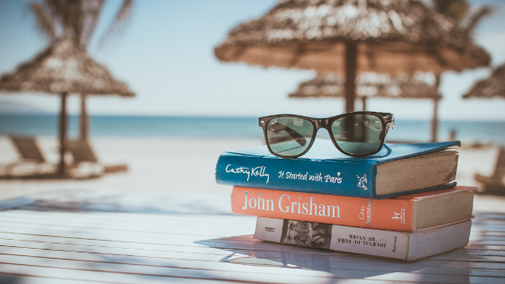 Beach scene with books and sunglasses