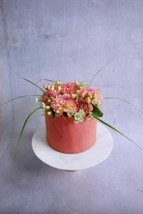 Torte in zartem Rot mit Blumenkrone