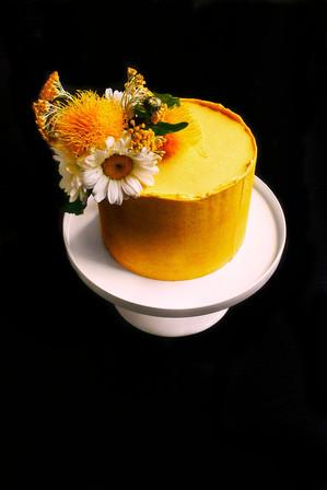 Gelbe Torte mit großem Blumenarrangement