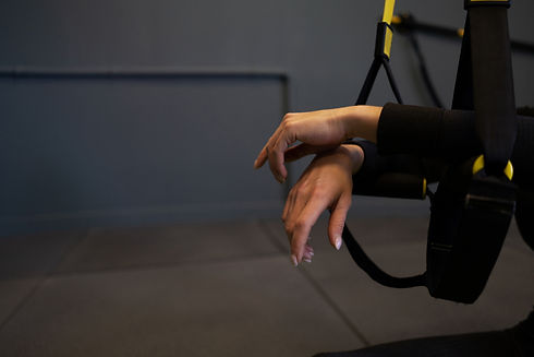 Cropped shot of female hands on trx stra