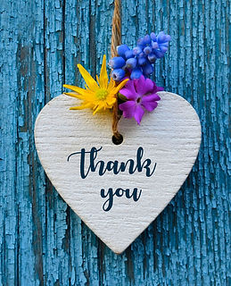 Thank You or thanks greeting card with flowers and decorative white heart on blue wooden b