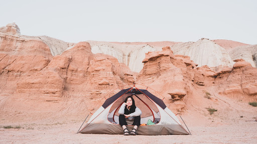 """Woman alone in tent facing toward camera with head resting on hand surrounded by a dry dessert. Not having the right gear or the money to pay for it can stop women from reaching their adventure goals. Check out our suggestions! <span>Photo by <a href=""""https://unsplash.com/@hammy?utm_source=unsplash&amp;utm_medium=referral&amp;utm_content=creditCopyText"""">Joshua Gresham</a> on <a href=""""https://unsplash.com/?utm_source=unsplash&amp;utm_medium=referral&amp;utm_content=creditCopyText"""">Unsplash</a></span>"""