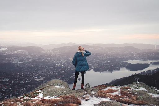 """Woman on mountain face looking down on the town below. The guilt felt from being away from your family or career can be an adventure-dream killer. But you need that time for you!  <span>Photo by <a href=""""https://unsplash.com/@sharon_christina?utm_source=unsplash&amp;utm_medium=referral&amp;utm_content=creditCopyText"""">Sharon Christina Rørvik</a> on <a href=""""https://unsplash.com/?utm_source=unsplash&amp;utm_medium=referral&amp;utm_content=creditCopyText"""">Unsplash</a></span>"""