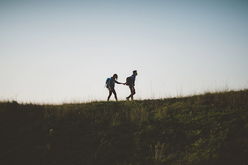 """Woman and man wearing backpacks on a walk through a grassy field. Woman is behind the man as he holds her hand and pulls her forward. So many women are afraid of harassment on their outdoor adventures... But it doesn't have to be too scary! Check out our tips for feeling safe.   <span>Photo by <a href=""""https://unsplash.com/@yulokchan?utm_source=unsplash&amp;utm_medium=referral&amp;utm_content=creditCopyText"""">Joseph Chan</a> on <a href=""""https://unsplash.com/?utm_source=unsplash&amp;utm_medium=referral&amp;utm_content=creditCopyText"""">Unsplash</a></span>"""