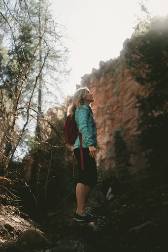 Woman on hike with teal backpack looking up a very large steep cliff. Self doubt and fear can be some of the biggest deterrents to women exploring and learning new skills.