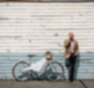 The Tiller Rides Roadster electric bike leaning against a wall in Fremantle while its rider speaks on the phone