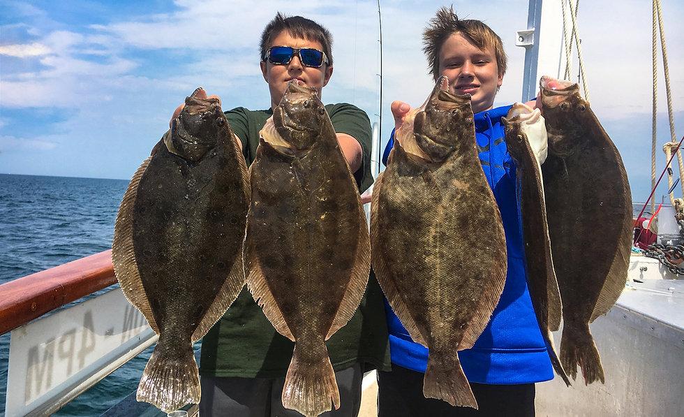 2 Children holding up giant fluke fish