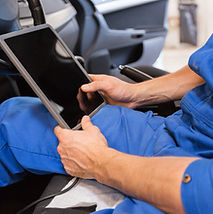 Automotive mechanic or technician using a scan tool to diagnose vehicle engine management faults.