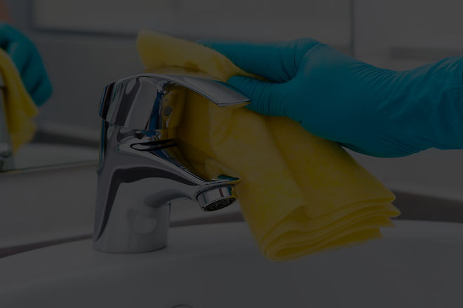 A gloved hand cleaning a faucet with a yellow towel