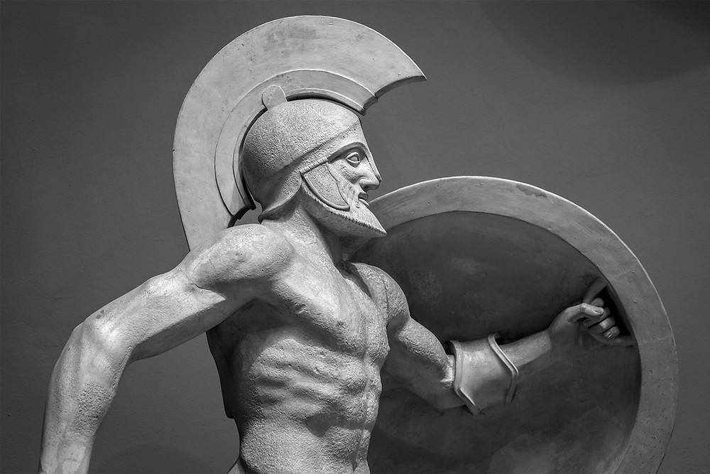 An ancient stoic soldier wearing a helmet and carrying a small round shield